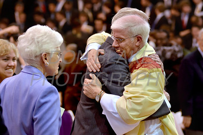 Mike Vogt hugs his father Albert Vogt as his mother Mary watches at the conclusion of his Ordination in the Gym of Salesianum School, Wilmington, Del., Friday, January 27, 2012. Mike Vogt ask Bishop Malooly for permission to have his Ordination in the gym of Salesianum School where he is a teacher. photo/Don Blake Photography.com