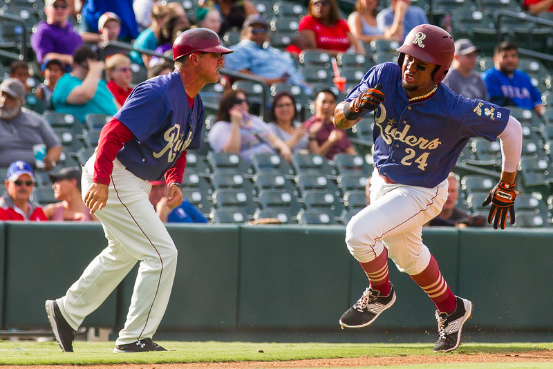 Frisco RoughRiders' Andy Ibanez (24) scores on Ronald Guzman's (not pictured) single in the first inning of an MiLB game against the Corpus Christi Hooks in Frisco, Texas, Sunday, June 26, 2016. Manager Joe Mikulik at left. (Photo by Sam Hodde)