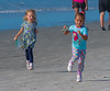 A couple of young girls on the run looking for seashells.