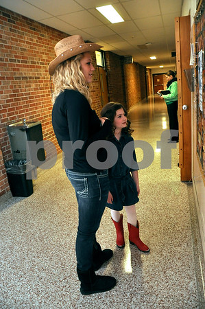 -Messenger photo by Joe Sutter<br /> <br /> Hannah Bird, 18, left, and Emma Krause, 7, take a moment to look at the board outside the dressing room before the pageant begins. Bird said she's been doing the pageant since second grade, and really enjoyed getting to help Krause this year.