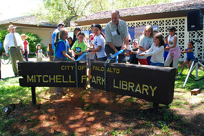 Palo Alto Mayor Pat Burt and local children break apart the old Mitchell Park Library sign.