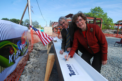 Becky and Jim Morgan sign the beam.