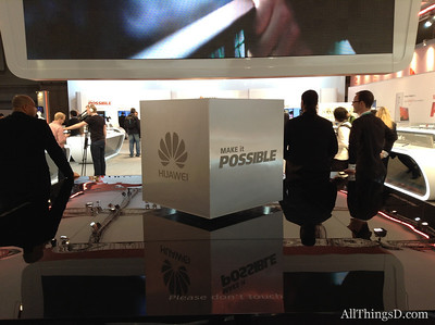 "Huawei's booth features, along with its devices, this levitating metal cube feature the company's new ""make it possible"" tagline."