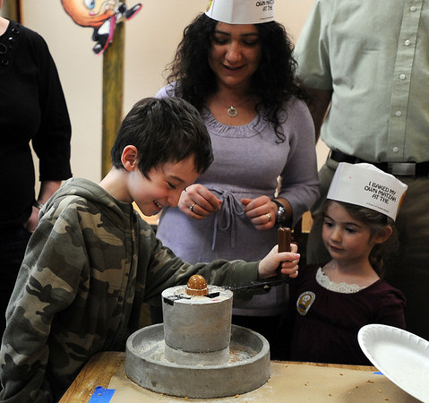 "Yotam Govrin, left, turns the wheat grinding wheel as mother Sofia, and Shirley Bierkatz, look on.<br /> The Model Matzah Bakery was brought to Boulder by Chabad Lubavitch of Boulder County. The bakery is an educational experience for the entire family to learn about the story and art of making matzah.<br /> For more photos and a video, go to  <a href=""http://www.dailycamera.com"">http://www.dailycamera.com</a>.<br /> Cliff Grassmick / March 14, 2010"