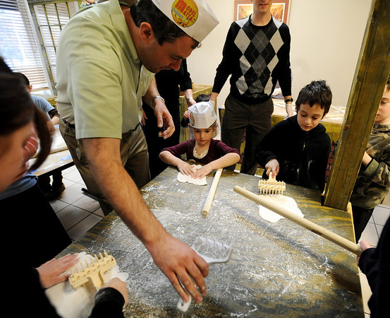 """Oren Bierkatz, left, helps his daughter, Shirley, and Yanir Govrin, right, with the hole punching process.<br /> The Model Matzah Bakery was brought to Boulder by Chabad Lubavitch of Boulder County. The bakery is an educational experience for the entire family to learn about the story and art of making matzah.<br /> For more photos and a video, go to  <a href=""""http://www.dailycamera.com"""">http://www.dailycamera.com</a>.<br /> Cliff Grassmick / March 14, 2010"""