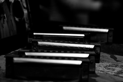 Harmonicas lined up on the piano.