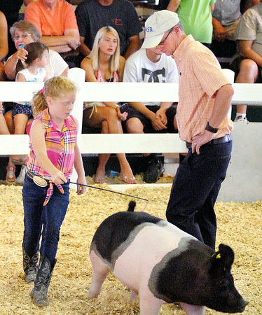 John P. Cleary | The Herald Bulletin<br /> Skyler Drake moves her pig around swine judge Steve Rodibaugh as he keeps a close eye on her animal during swine judging Monday at the 4-H Fair.<br /> For a gallery of photos to view or purchase, visit<br /> photos.heraldbulletin.com.