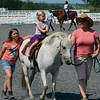 Mia Gibney enjoys a pony ride with 4-H Horse and Pony Club members Jill Steeley (R) and her daughter Samantha Fry (L)  during the Montgomery County 4-H Fair in Skippack Township on Saturday August 9,2014. Photo by Mark C Psoras