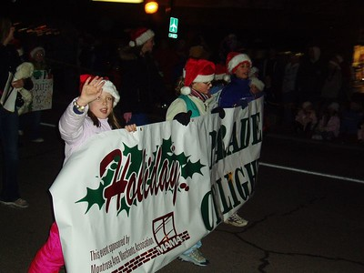 Andrea (in the middle) marching with her girl scout troup -- carrying the sign the kicked off the parade
