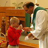 Third-grader Adam Boyd receives Holy Communion from the cup from Deacon Michael Prier.