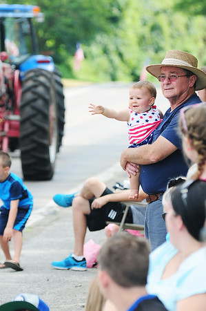 Richard Eidam of North Beaver Township holds his 9 month old grand daughter Claire Copper who is also from North Beaver Township, while they watch the tractors in Saturday's parade.