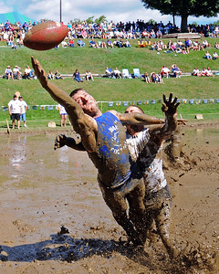 A MWV Hogs receiver stretches for a pass in a game vs the Muddas Football Club, on Sept. 10th, during The 35th Annual World Championship of Mud Football, which was held September 9th thru 11th, 2011, on Steve Eastman Field at Hog Coliseum, in North Conway, New Hampshire.
