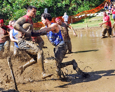 A Mud Skippers player is stopped by a Cumberland (RI) Muckaneer defender, after gaining a 1st down, in a Sept. 10th game, during The 35th Annual World Championship of Mud Football, which was held September 9th thru 11th, 2011, on Steve Eastman Field at Hog Coliseum, in North Conway, New Hampshire.