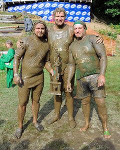 Shortly after their Nashua Mud Gumbys defeated the Muddas Football Club, 12-10, to win The 35th Annual World Championship of Mud Football on September 11th, 2011, players (from left), Mike Leyenaar & brother Brad, along with teammate Rob Hayden, pose with their Championship Trophy on Steve Eastman Field at Hog Coliseum, in North Conway, New Hampshire.