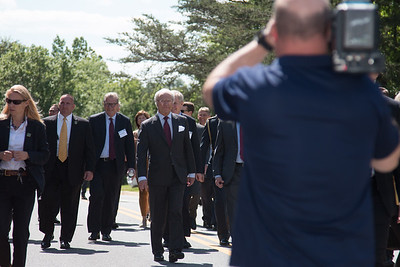 The King wlks briskly (only person without an ID lanyard!) -- King Carl XVI Gustaf of Sweden visited NASA/Goddard on May 3, 2017.  These photos show his short walking procession from viewing the Hyperwall in Building 28 to the clean room facility in Building 29.