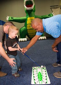 Alvin Queen teaches 3 year old JT the finer points of golf at a booth sponsored by GolfDC.Academy.