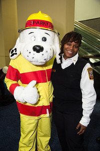 Sparky the fire dog mascot poses with D.C. Fire Department Inspector Ursala Brimage. Sparky teaches about fire safety, including escape routes, and smoke alarms.