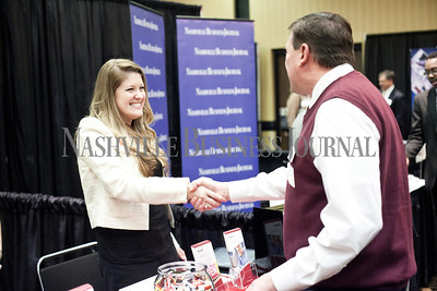 Erin Cox of Ascend Federal Credit Union shakes hands with a pre-existing client Tom Starling, of Mental Health America of Middle TN  during the Nashville Business Journal's first Business Growth Expo at the Nashville Convention Center Wednesday. More than 40 businesses represented. Nathan Morgan | Nashville Business Journal