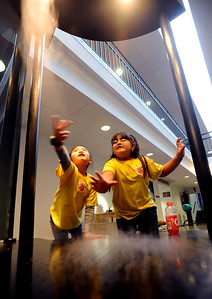 """Alista Yang, left, and Dulce Quezada, both second-graders from Rocky Mountain Elementary in Westminster, break up the airflow of the """"tornado"""" in the miniature tornado machine at the NCAR Visitors Center on Thursday. NCAR (National Center for Atmospheric Research), located in Boulder, will celebrate 50 years of existence this summer. For more photos and a video, go to www.dailycamera.com. Cliff Grassmick/ January 21, 2010."""