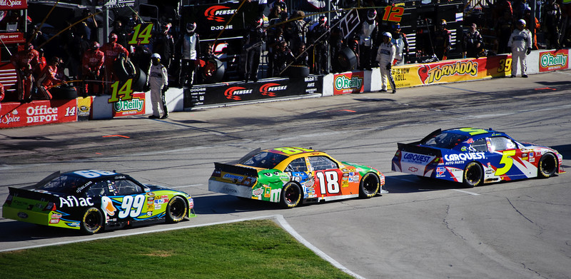Carl Edwards (99), Kyle Busch (18) and Mark Martin (5) on pit road.