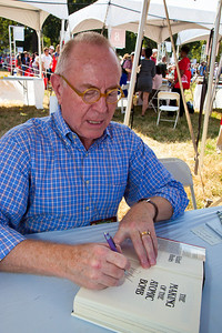 "Richard Rhodes signs books at the National Book Festival. He is the author or editor of more than 20 books, including ""The Making of the Atomic Bomb,"" which won a Pulitzer Prize in Nonfiction, a National Book Award and a National Book Critics Circle Award. ""The Twilight of the Bombs: Recent Challenges, New Dangers and the Prospects of a World Without Nuclear Weapons"" (Knopf), has just been published. The 10th annual National Book Festival, organized and sponsored by the Library of Congress, was held on Saturday, Sept. 25, 2010, on the National Mall in Washington, D.C. (Photo by Jeff Malet)."