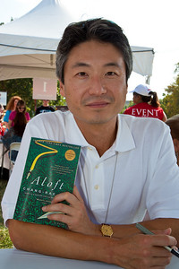 "Chang-rae Lee signs books at the National Book Festival. After graduating from prep school, Chang-rae Lee entered Yale University in 1983. He majored in English and wrote short stories on his own time, but he never showed them to anyone. He took a job on Wall Street in 1987, but the work was unfulfilling, so he resigned and decided to work on a novel. That novel was never published, but his next one, ""Native Speaker,"" was. ""Native Speaker"" won the American Book Award and the Hemingway Foundation/PEN Award. The New Yorker and Granta magazines once named him one of the 20 best American writers under 40. The New York Times said, ""The book has been acclaimed as a lyrical, edgy and perceptive tale of the second-generation foreigner, the child of immigrants stranded in a no-man's-land between the old culture and the new."" His new novel is ""Surrendered"" (Penguin, Riverhead).  The 10th annual National Book Festival, organized and sponsored by the Library of Congress, was held on Saturday, Sept. 25, 2010, on the National Mall in Washington, D.C. (Photo by Jeff Malet)."