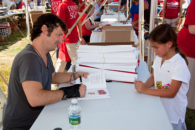 "Jeff Smith signs a book at the National Book Festival for young Emma Shacochis of Herndon Va. The 10th annual National Book Festival, organized and sponsored by the Library of Congress, was held on Saturday, Sept. 25, 2010, on the National Mall in Washington, D.C. A co-founder of the 1990s self-publishing movement and an early adopter of the graphic novel format, Jeff Smith is best known as the writer and artist of ""BONE,"" an award- winning adventure about three cartoon cousins lost in a world of myth and ancient mysteries. In 2008, Smith was the subject of a documentary called ""The Cartoonist: Jeff Smith, BONE, and the Changing Face of Comics."" Besides ""BONE"" and ""RASL,"" his other books include ""Shazam: The Monster Society of Evil"" and ""Little Mouse Gets Ready!""  (Photo by Jeff Malet)."