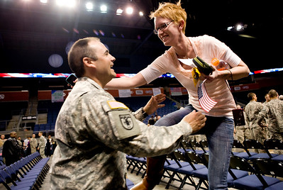 1st Lt. Timber Toste catches his wife, Jessica Toste, as she jumps over the chair after National Guard homecoming ceremony at the 1st Bank Center in Broomfield, Thursday, April 1, 2010. Toste just returned from a tour in Iraq.