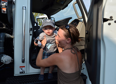 Milena Snapp helps her son Vonn, 1, get out of a street sweeper during the National Night Out Picnic in the Park at Broomfield County Commons Park on Tuesday.  August 7, 2012 staff photo/ David R. Jennings
