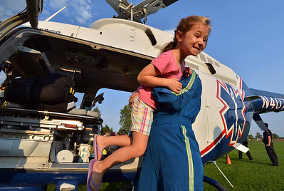 Cecilia Guerrera, 5, is helped out of the AirLife helicopter by EMT-B  Taylor Mustachio, right, during the National Night Out Picnic in the Park at Broomfield County Commons Park on Tuesday.   August 7, 2012 staff photo/ David R. Jennings