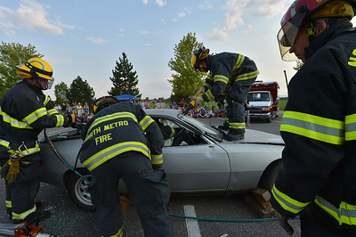 North Metro Fire Rescue firefighter Rob Perry stands on the hood of a car for an extrication demonstration during the National Night Out Picnic in the Park at Broomfield County Commons Park on Tuesday.   August 7, 2012 staff photo/ David R. Jennings