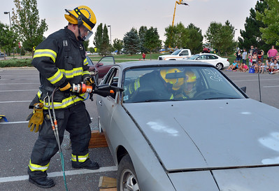 North Metro Fire Rescue firefighter Paul Strongwater begins to take off the roof of a car for an extrication demonstration during the National Night Out Picnic in the Park at Broomfield County Commons Park on Tuesday.  August 7, 2012 staff photo/ David R. Jennings