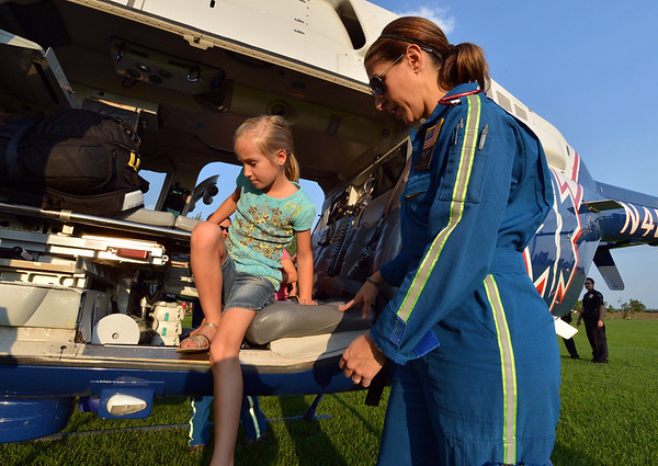 AirLife EMT-B  Taylor Mustachio, right, helps Tess Guerrera, 7, out of the helicopter during the National Night Out Picnic in the Park at Broomfield County Commons Park on Tuesday.<br /> <br /> August 7, 2012<br /> staff photo/ David R. Jennings