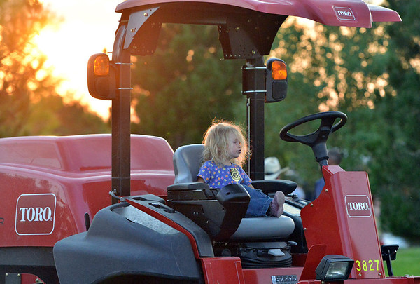 Phoebe Bellanger, 2, sits in a lawn mower  during the National Night Out Picnic in the Park at Broomfield County Commons Park on Tuesday.<br /> <br /> August 7, 2012<br /> staff photo/ David R. Jennings