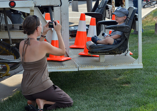 Milena Snapp, left, takes a picture of her son Vonn, 1, sitting on a street painting truck during the National Night Out Picnic in the Park at Broomfield County Commons Park on Tuesday.<br /> <br /> August 7, 2012<br /> staff photo/ David R. Jennings