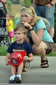 Kelly O'Keefe points out to her son Conor Martau, 5, what North Metro Fire Rescue firefighters are doing during an automobile extrication at the National Night Out Picnic in the Park at Broomfield County Commons Park on Tuesday.  August 7, 2012 staff photo/ David R. Jennings