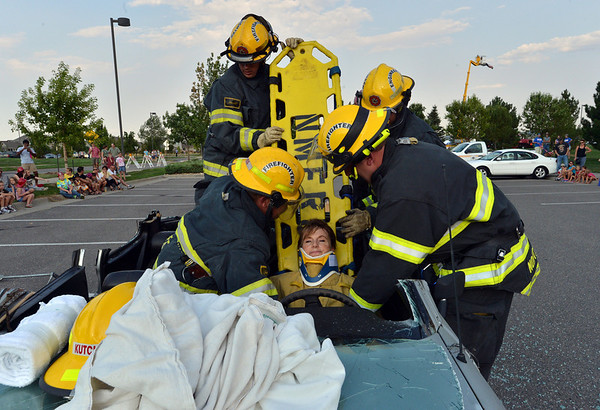 North Metro Fire Rescue District's Pam Kutchen plays the victim for firefighters for an extrication demonstration during the National Night Out Picnic in the Park at Broomfield County Commons Park on Tuesday.<br /> <br /> August 7, 2012<br /> staff photo/ David R. Jennings