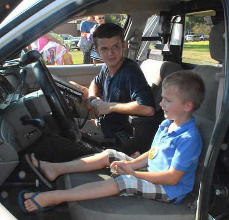 Diane Raver | The Herald-Tribune<br /> Brice Keaton (left), a member of Batesville Law Enforcement Explorer Post 683, talks to Russell Grubbs, 5, who is enjoying the opportunity to sit in a police car.