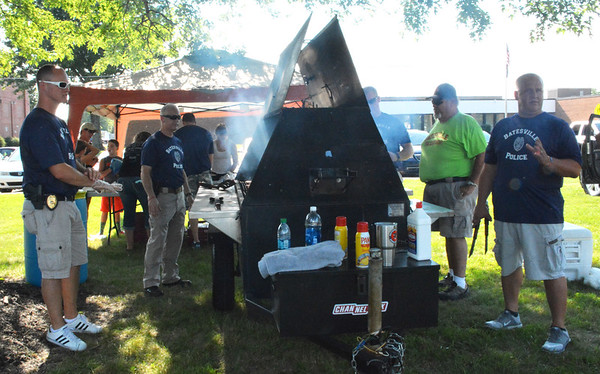 "Diane Raver | The Herald-Tribune<br /> Maj. Mike Benjamin (from left), Chief Stan Holt, Patrolman Mike Manus, Robert ""Tuba"" Narwold and Cpl. Dave Abel take their turns at the grill."