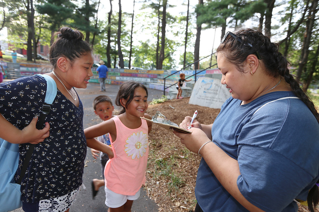 . National Night Out, at North Common, organized by the Lowell Police Department. From left, Thar Mu, 11, of Lowell, looks on as Frances Nieves, 8, of Lowell, signs up for the talent show with Mu\'s sister, Kiss Quick, 18, of Lowell, who was keeping track of entrants. (SUN/Julia Malakie)