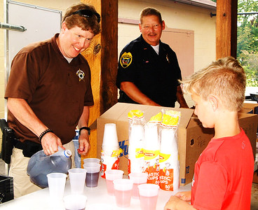 Debbie Blank | The Herald-Tribune Franklin County Sheriff's Department Deputy Sgt. Jason Lovins pours a drink for Ray Walke, 9, Oldenburg, while Oldenburg Deputy Lt. Eric Moenter gives food to others in line.
