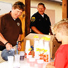 Debbie Blank | The Herald-Tribune<br /> Franklin County Sheriff's Department Deputy Sgt. Jason Lovins pours a drink for Ray Walke, 9, Oldenburg, while Oldenburg Deputy Lt. Eric Moenter gives food to others in line.