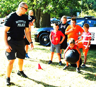 Diane Raver | The Herald-Tribune Batesville Patrolman Travis Cook gets kids ready for the obstacle course.