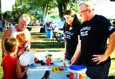Diane Raver | The Herald-Tribune Batesville Police Department Sgt. Chris Smith (right) and his daughter, Madison, show kids how to examine fingerprints.