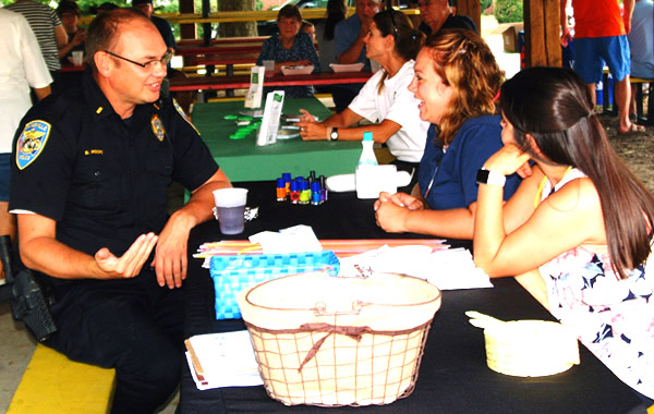 Debbie Blank | The Herald-Tribune<br /> Batesville Police Department Lt. Detective Blake Roope (from left) visits with Margaret Mary Health community outreach registered nurse Meg Applegate and community health improvement clerk Megan Whitaker, who were distributing free drug testing kits and details about the Lock Your Meds initiative.