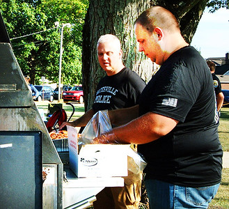 Diane Raver | The Herald-Tribune Batesville Police Chief Stan Holt (left) and Cpl. Ryan Metcalf grill hot dogs and hamburgers.