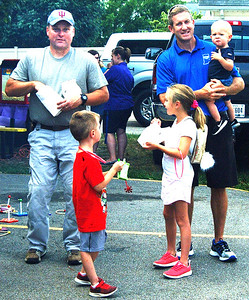 Debbie Blank | The Herald-Tribune Franklin County Sheriff Peter Cates (left) and Prosecutor Chris Huerkamp were greeting the crowd and munching on popcorn in Oldenburg. With the county prosecutor are his three children, Lena, 7; Will, 5; and Nick, 1.