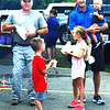 Debbie Blank | The Herald-Tribune<br /> Franklin County Sheriff Peter Cates (left) and Prosecutor Chris Huerkamp were greeting the crowd and munching on popcorn in Oldenburg. With the county prosecutor are his three children, Lena, 7; Will, 5; and Nick, 1.