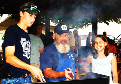 Debbie Blank | The Herald-Tribune Charlotte Trossman (from right), 11, Oldenburg, watches as grandpa Eddie Obermeyer, a Knights of St. John volunteer, and Austin Lovins, 17, Brookville, son of Franklin County Sheriff's Department Deputy Sgt. Jason Lovins, keep an eye on hamburgers and cheeseburgers on the grill at the Oldenburg shelterhouse.