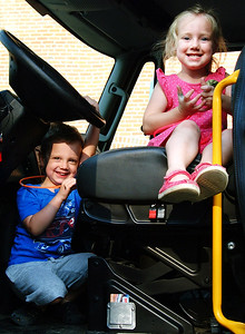 Debbie Blank | The Herald-Tribune Griffin Dunn (left), 3, Batesville, and sister Dyllan, 4, imagine what it would be like to be firetruck drivers inside an Eagle Fire Co. vehicle.